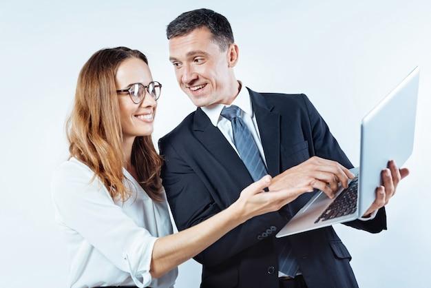 O trabalho em equipe é o trabalho dos sonhos. colegas de trabalho alegres, sorrindo alegremente enquanto usam um laptop e colaboram em um problema de projeto de negócios.