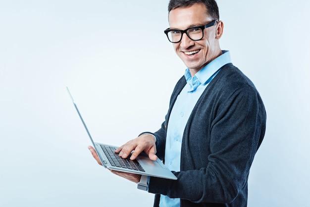 O trabalho está chamando. vista lateral de um empresário de sucesso virando a cabeça para a câmera e sorrindo enquanto trabalhava em um projeto com o computador nas mãos.