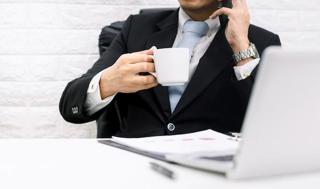O trabalho executivo do empresário da pausa para o café relaxa segure o telefone no laptop em sua mesa.