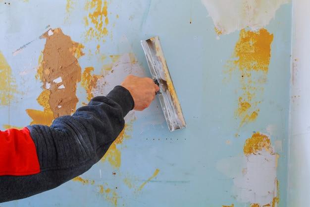 O trabalho se alinha. colocando gesso na parede com espátula