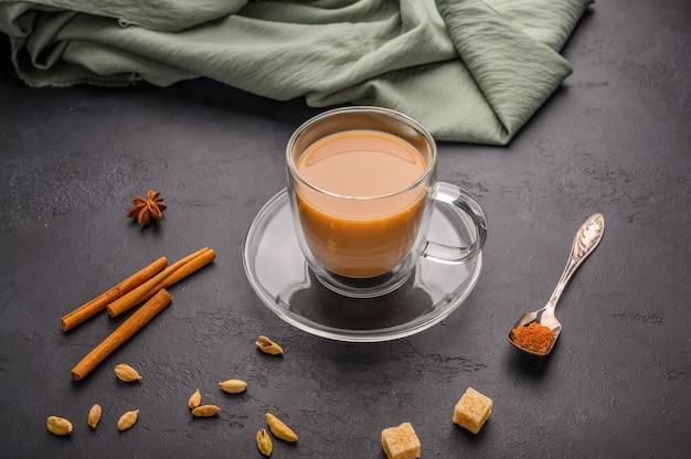 O tradicional chá indiano masala chai em uma xícara transparente é um close-up