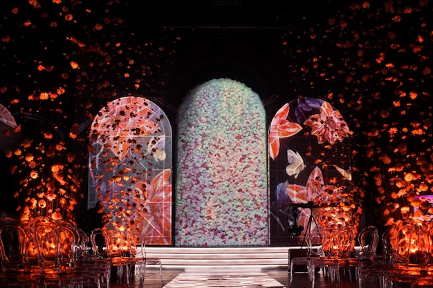 O trajeto do relance conduz aos archs brilhantes com flores no quarto escuro