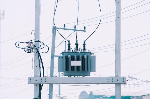 O transformer está localizado em um poste alto com um fundo de céu claro.