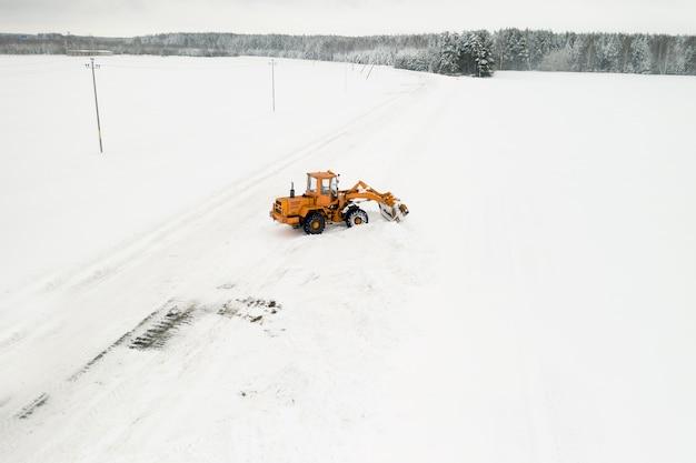 O trator amarelo com um balde remove a neve da vista superior da estrada.