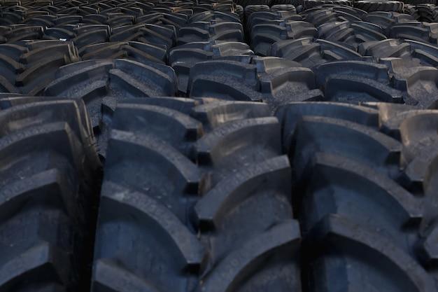 O trator cansa com um grande protetor, em um grande armazém de máquinas agrícolas.