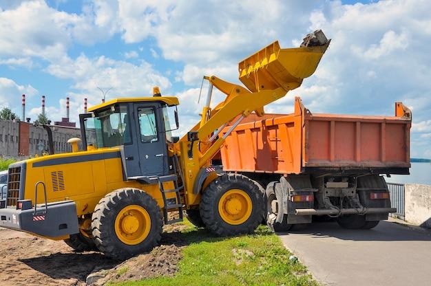 O trator carrega o solo no caminhão basculante. reparos em estradas