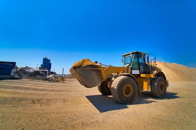 O trator coleta uma concha com cascalho. a escavadeira extrai areia e cascalho para a mistura de concreto