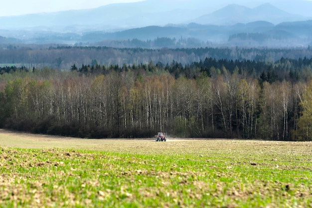 O trator com a unidade espalha fertilizante mineral no campo