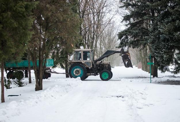 O trator com um trailer no inverno no jardim botânico limpa a estrada de neve e galhos.