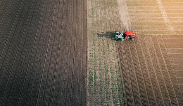 O trator com uma semeadora prepara o terreno para a semeadura de grãos em campo arado. vista aérea.