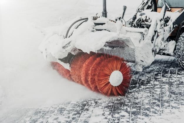O trator limpa a estrada da neve após nevasca ou forte nevasca. limpando ou lavrando a neve