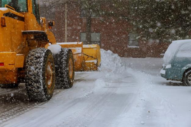 O trator limpa a estrada depois de uma nevasca