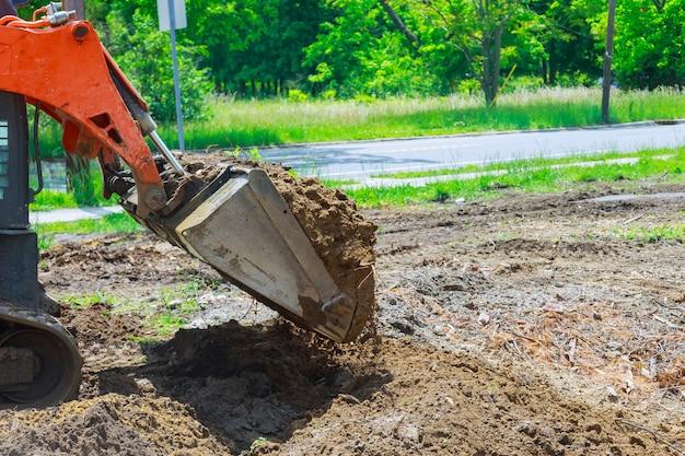 O trator move o equipamento de construção do solo para escavar o solo