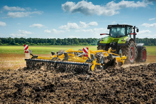 O trator puxa um cultivador de discos, o sistema de preparo do solo no campo se prepara para a nova safra