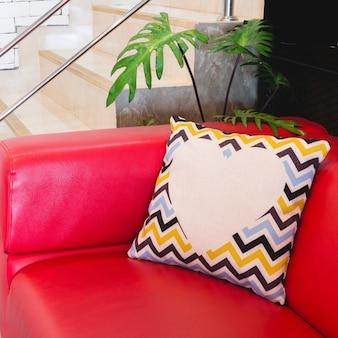 O travesseiro colorido do projeto moderno pôs sobre o sofá luxuoso vermelho.