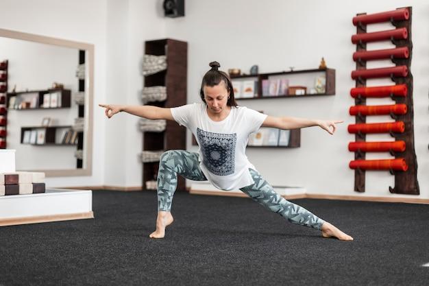 O treinador atlético jovem faz exercícios de alongamento de barbante. a menina aquece os músculos. ioga e estilo de vida saudável