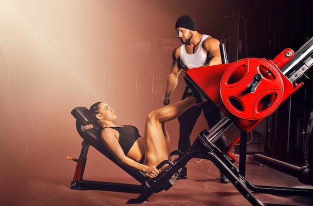 O treinador controla a execução do exercício. preparando um atleta para competições.