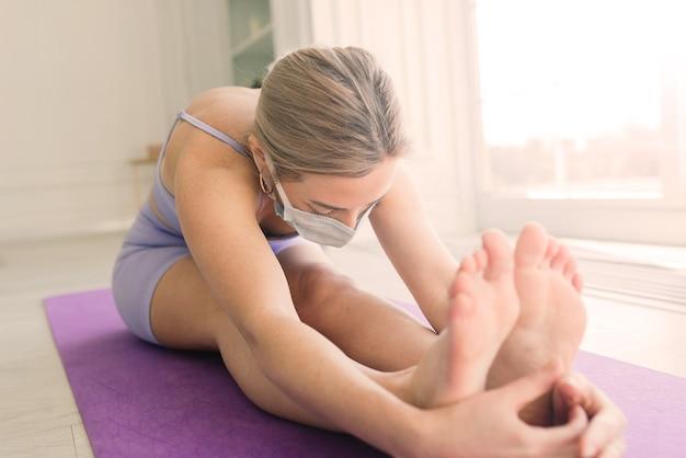 O treinador de fitness de esporte feminino atraente usando máscara médica branca faz exercícios no tapete de ioga em uma casa.
