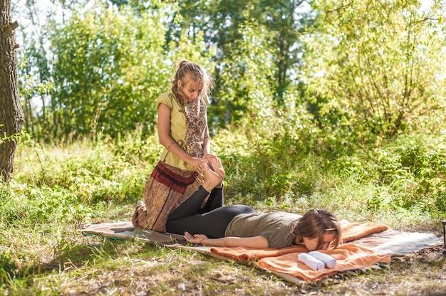 O treinador de massagens demonstra métodos de massagem revigorantes ao ar livre.