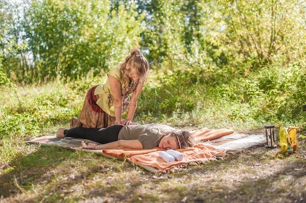 O treinador de massagens demonstra métodos de massagem revigorantes em uma clareira na floresta.