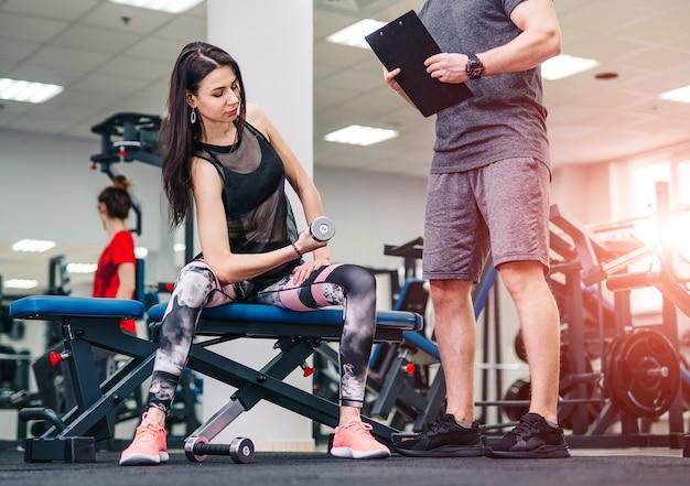 O treinador e a garota fitness estão se exercitando na academia.