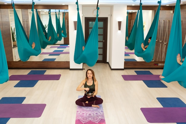 O treinador ioga com a taça da meditação introduz suas proteções em transe. mosca ioga exercícios de alongamento no ginásio. estilo de vida apto e bem-estar