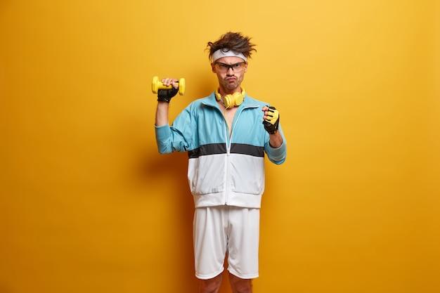 O treinador severo e sério conduz o treinamento físico, fecha os punhos com raiva, levanta halteres com uma das mãos, vestido com roupas esportivas, faz levantamento de peso, isolado sobre a parede amarela esporte, treino