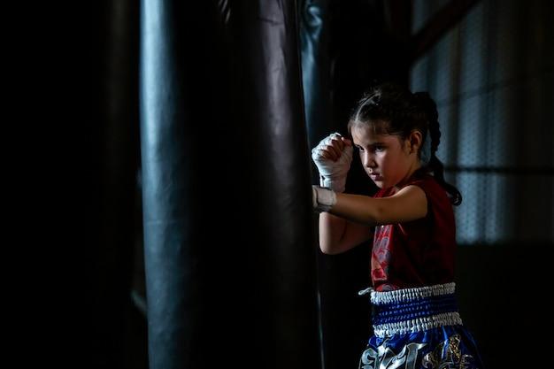 O treinamento tailandês pequeno do encaixotamento da menina é um curso da autodefesa, muay thai.