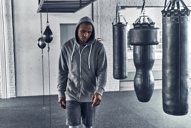 O treino acabou. africano jovem cansado em roupas esportivas, caminhando enquanto faz exercícios na academia