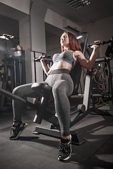 O treino de levantamento de peso fitness mulher no ginásio