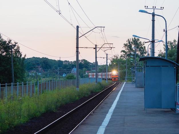 O trem chega na plataforma da estação da vila à noite