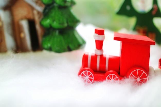 O trem de madeira vermelho correndo na neve com pinheiro e casa de madeira.
