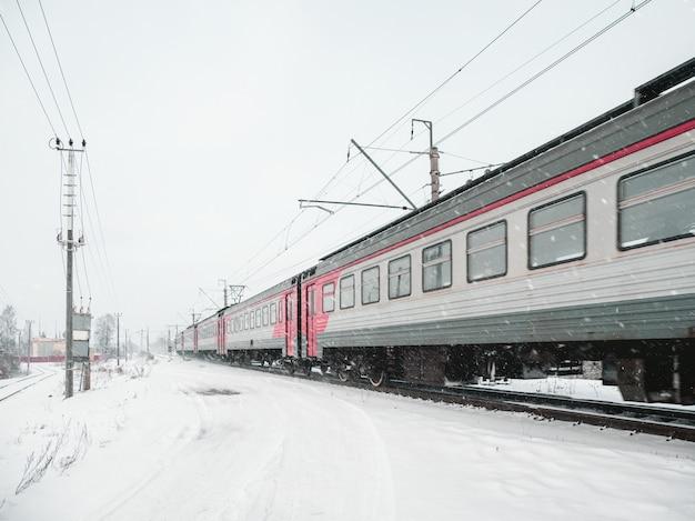 O trem está em movimento em um dia nevado de inverno.