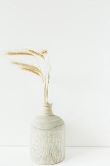 O trigo pica o buquê em um vaso de madeira em branco.