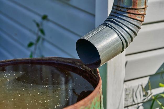 O tubo de drenagem está conectado a um barril de ferro enferrujado com água da chuva