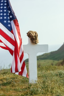 O túmulo de um soldado. bandeira americana sobre o túmulo do soldado falecido. no túmulo, um boné militar