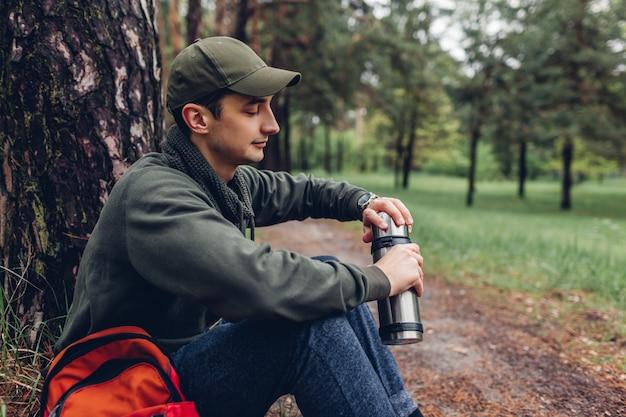 O turista do homem abre a garrafa térmica com chá quente na floresta da mola acampamento, viajando