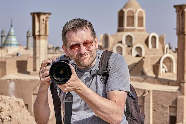 O turista ergueu a câmera até o nível do rosto e está procurando um objeto para fotografar em uma cidade antiga.