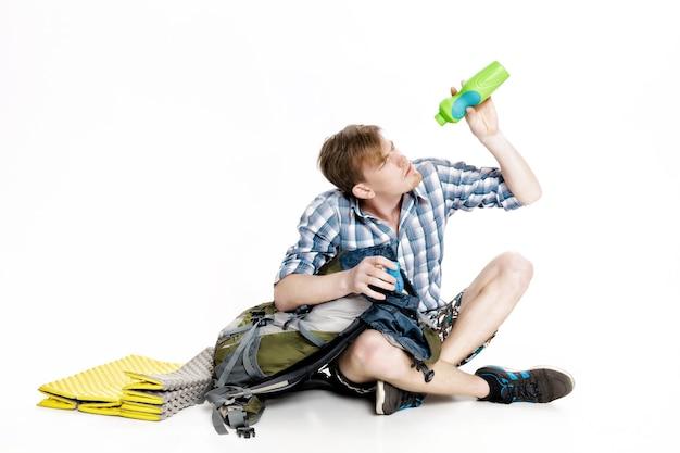 O turista está com sede. o viajante quer beber água, mas acabou a água