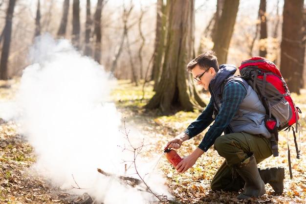 O turista sacia o fogo do extintor de incêndio, depois de um descanso na natureza