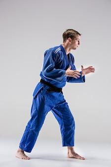 O um lutador de judocas posando em cinza