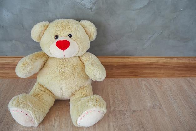 O ursinho de pelúcia está sentado num chão de madeira.