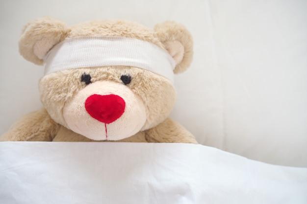O ursinho de pelúcia tem gaze na cabeça