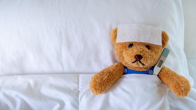 O ursinho dormiu com febre alta na cama. juntamente com um termômetro.