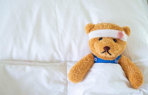 O ursinho estava doente na cama depois de ser ferido em um acidente. conceito de seguro de vida e seguro de acidentes