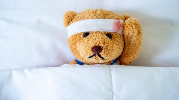 O ursinho estava doente na cama depois de ser ferido em um acidente. obtendo o seguro de vida e o conceito de seguro contra acidentes