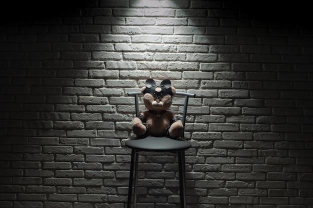 O urso de brinquedo vestido com um acessório de alças de couro para jogos de bdsm sob luz forte contra uma parede de tijolos