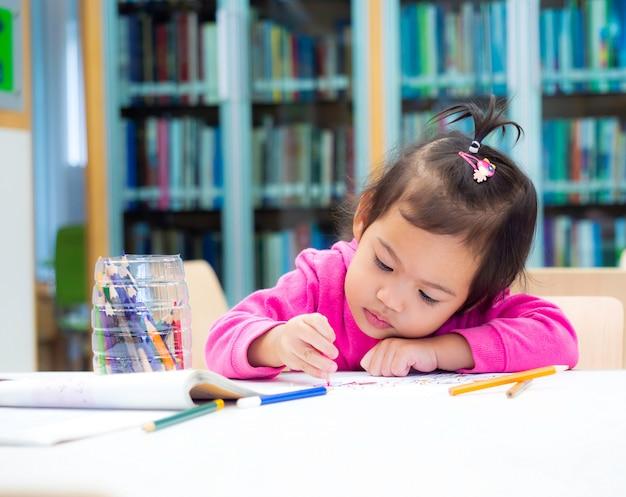 O uso bonito da menina do bebê pequeno colore o desenho de lápis no livro branco na biblioteca.