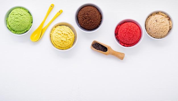 O vário da bola do sabor do gelado estabelece-se no fundo de madeira branco.