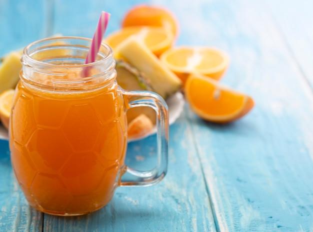 O vaso de vidro com o suco de laranja com um canudo em uma mesa azul